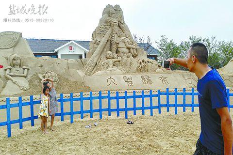 7月9日上午,一位游客为两个孩子在一个动漫题材沙雕前留影.